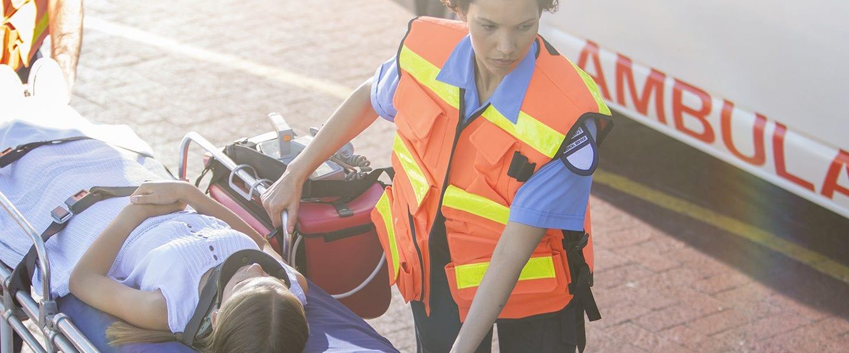 Paramedics wheeling patient in hospital parking lot