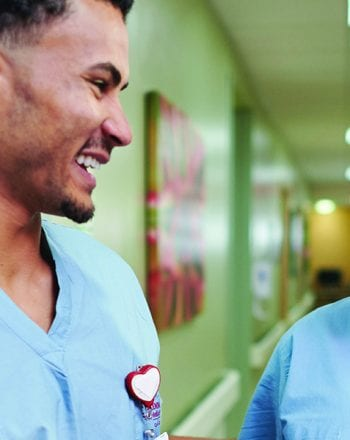 Health care professionals greet each other in a hallway